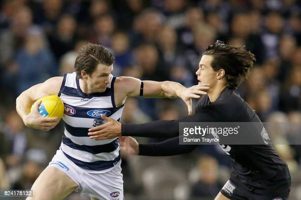 Patrick Dangerfield of the Cats evades Jack Silvagni of the Blues during the round 19 AFL match between the Carlton Blues and the Geelong Cats at...