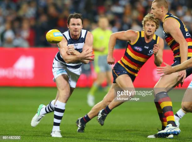 Patrick Dangerfield of the Cats handballs away from Rory Sloane of the Crows during the round 11 AFL match between the Geelong Cats and the Adelaide...