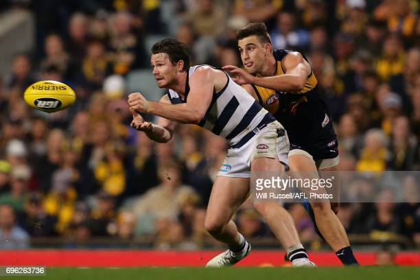 Patrick Dangerfield of the Cats handpasses the ball under pressure from Elliot Yeo of the Eagles during the round 13 AFL match between the West Coast...
