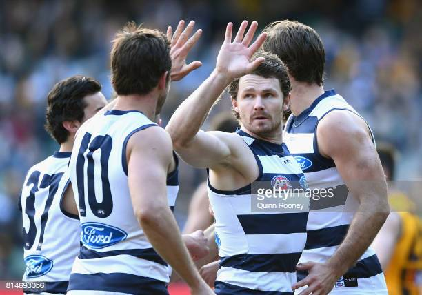Patrick Dangerfield of the Cats is congratulated by team mates after kicking a goal during the round 17 AFL match between the Geelong Cats and the...