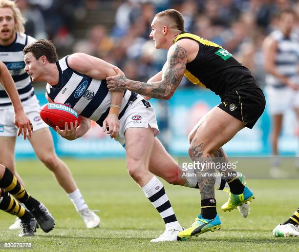 Patrick Dangerfield of the Cats is tackled by Dustin Martin of the Tigers during the 2017 AFL round 21 match between the Geelong Cats and the...