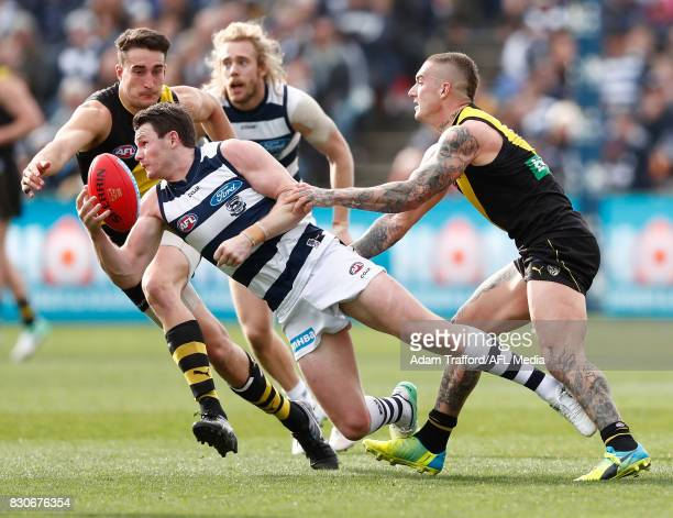 Patrick Dangerfield of the Cats is tackled by Ivan Soldo and Dustin Martin of the Tigers during the 2017 AFL round 21 match between the Geelong Cats...