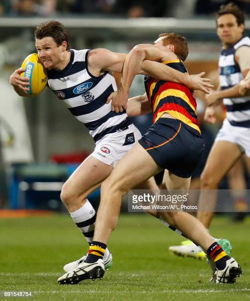 Patrick Dangerfield of the Cats is tackled by Tom Lynch of the Crows during the 2017 AFL round 11 match between the Geelong Cats and the Adelaide...