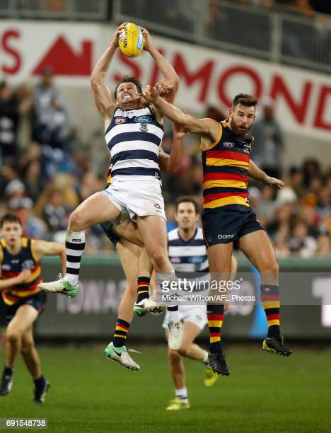 Patrick Dangerfield of the Cats marks the ball over Andy Otten of the Crows during the 2017 AFL round 11 match between the Geelong Cats and the...