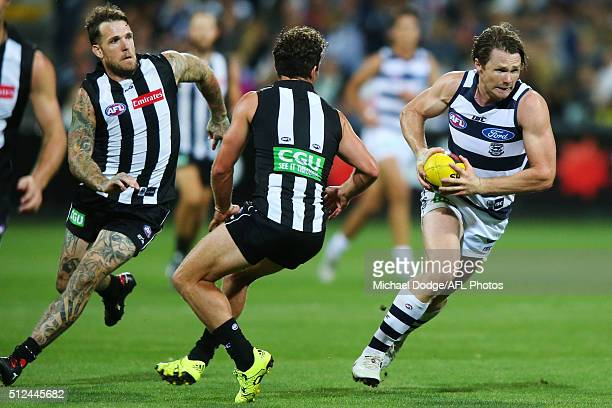 Patrick Dangerfield of the Cats runs with the ball away Dane Swan of the Magpies and Jarryd Blair during the 2016 NAB Challenge match between the...