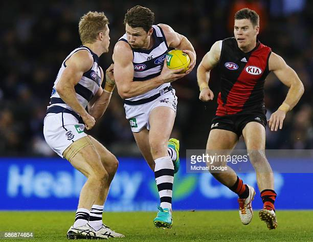 Patrick Dangerfield of the Cats runs with the ball away from Craig Bird of the Bombers during the round 20 AFL match between the Geelong Cats and the...
