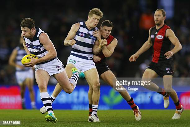 Patrick Dangerfield of the Cats runs with the ball away from Craig Bird of the Bombers as Scott Selwood of the Cats shepherds during the round 20 AFL...
