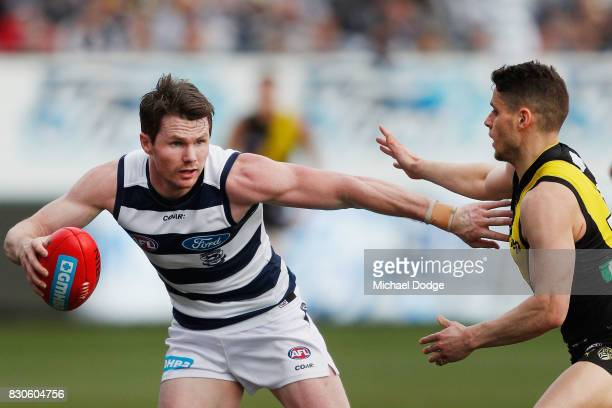 Patrick Dangerfield of the Cats runs with the ball past Dion Prestia of the Tigers during the round 21 AFL match between the Geelong Cats and the...