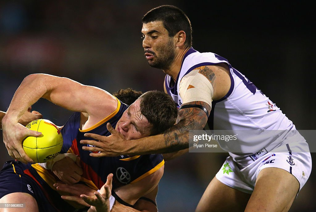 Patrick Dangerfield of the Crows is tackled by Clancee Pearce of the Dockers during the AFL Second Semi Final match between the Adelaide Crows and the Fremantle Dockers at AAMI Stadium on September 14, 2012 in Adelaide, Australia.