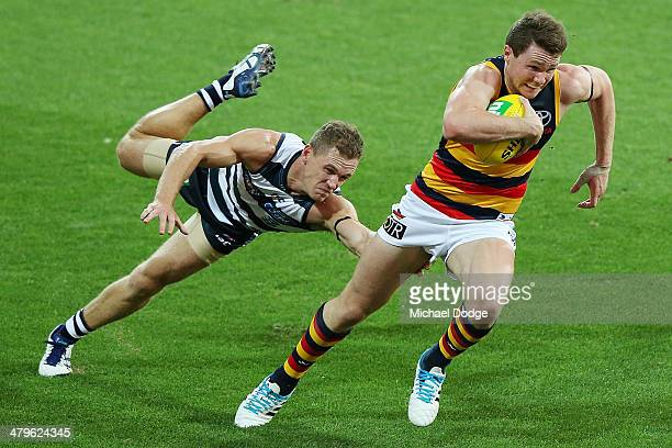 Patrick Dangerfield of the Crows runs away with the ball from Joel Selwood of the Cats during the round one AFL match between the Geelong Cats and...