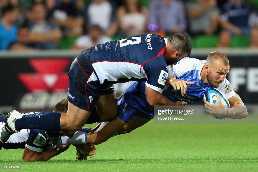 Patrick Dellit of the Force is tackled by Laurie Weeks of the Rebels during the round one Super Rugby match between the Rebels and the Force at AAMI Park on February 15, 2013 in Melbourne, Australia.