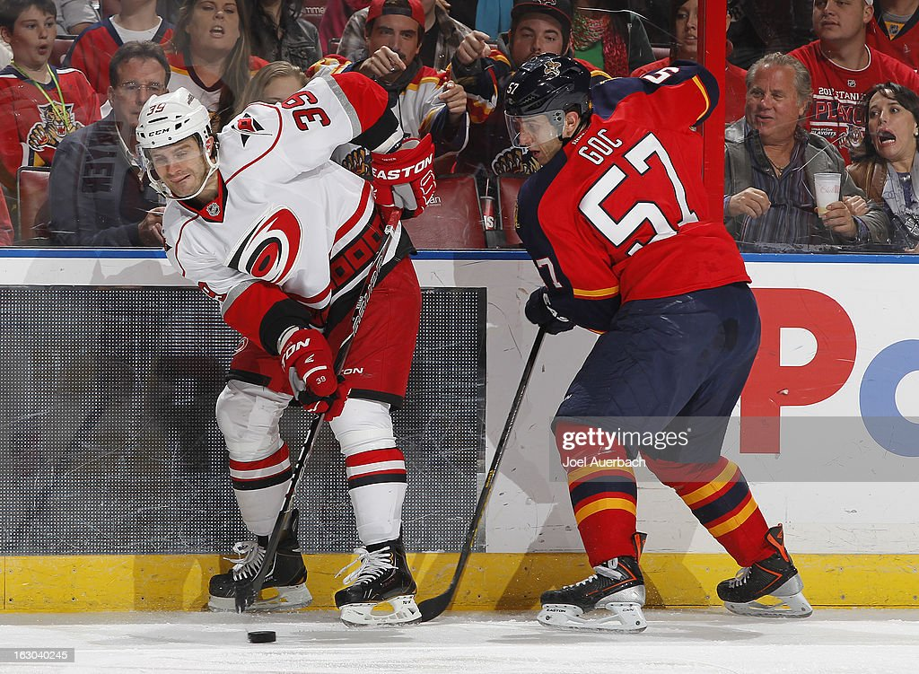 Patrick Dwyer #39 of the Carolina Hurricanes and <a gi-track='captionPersonalityLinkClicked' href=/galleries/search?phrase=Marcel+Goc&family=editorial&specificpeople=541626 ng-click='$event.stopPropagation()'>Marcel Goc</a> #57 of the Florida Panthers skate after a loose puck along the boards at the BB&T Center on March 3, 2013 in Sunrise, Florida. The Hurricanes defeated the Panthers 3-2.