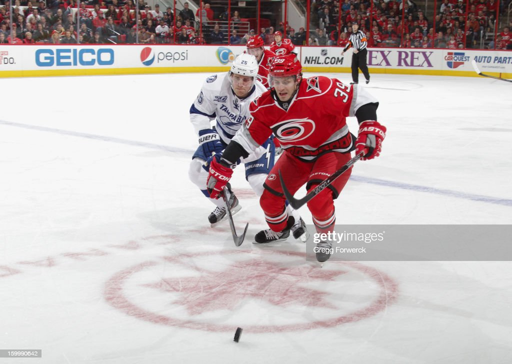 Patrick Dwyer #39 of the Carolina Hurricanes and Matthew Carle #25 of the Tampa Bay Lightning battle for a loose puck during their NHL game at PNC Arena on January 22, 2013 in Raleigh, North Carolina.