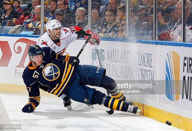 Patrick Dwyer of the Carolina Hurricanes battles for the puck with Tyler Myers of the Buffalo Sabres during their NHL game at First Niagara Center...