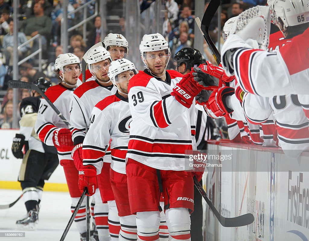 Patrick Dwyer #39 of the Carolina Hurricanes celebrates with the bench after a goal by <a gi-track='captionPersonalityLinkClicked' href=/galleries/search?phrase=Nathan+Gerbe&family=editorial&specificpeople=697084 ng-click='$event.stopPropagation()'>Nathan Gerbe</a> #14 during the third period against the Pittsburgh Penguins on October 8, 2013 at Consol Energy Center in Pittsburgh, Pennsylvania.