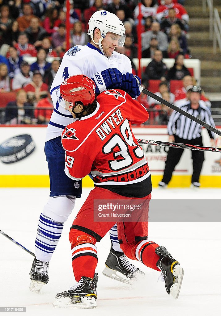 Patrick Dwyer #39 of the Carolina Hurricanes checks <a gi-track='captionPersonalityLinkClicked' href=/galleries/search?phrase=Cody+Franson&family=editorial&specificpeople=2125769 ng-click='$event.stopPropagation()'>Cody Franson</a> #4 of the Toronto Maple Leafs near center ice during play at PNC Arena on February 14, 2013 in Raleigh, North Carolina.