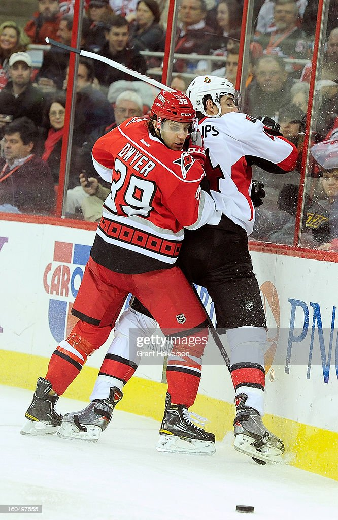 Patrick Dwyer #39 of the Carolina Hurricanes drives Chris Phillips #4 of the Ottowa Senators into the boards during play at PNC Arena on February 1, 2013 in Raleigh, North Carolina.