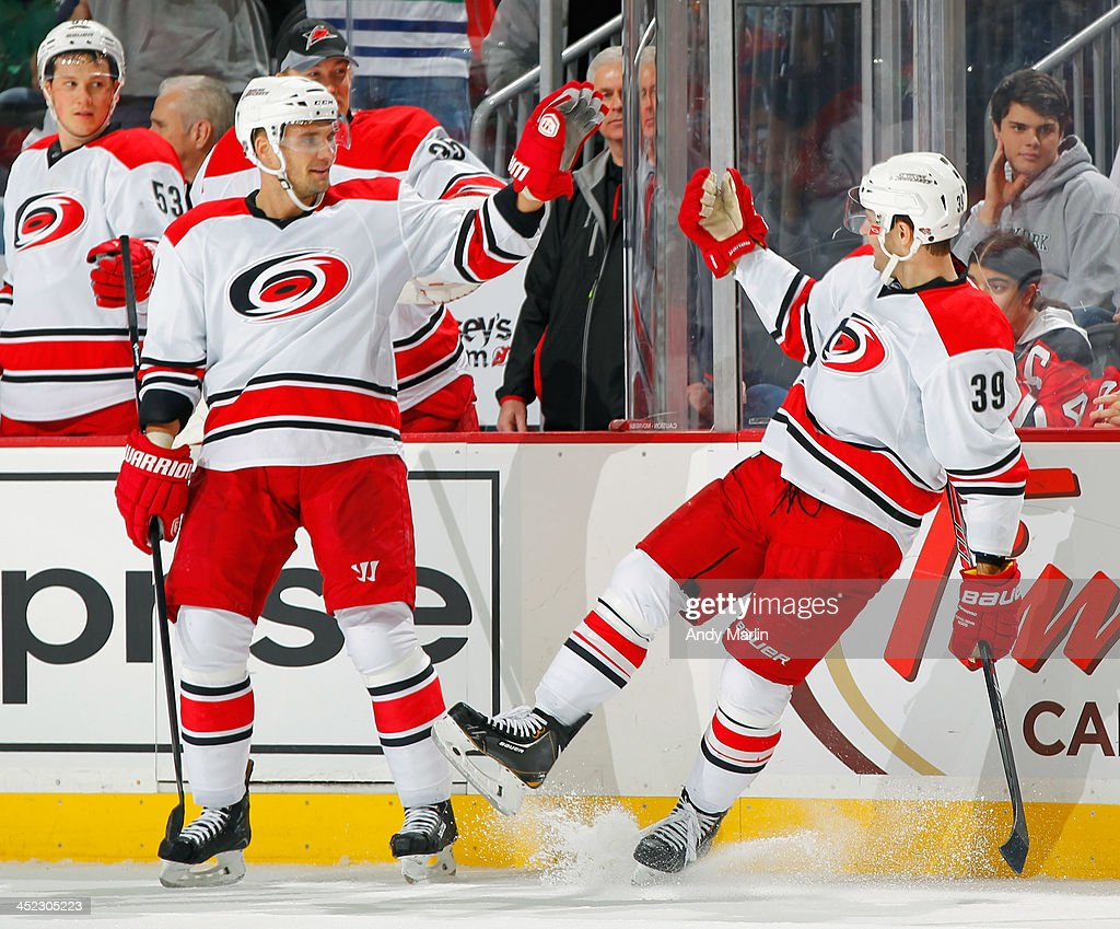 Patrick Dwyer #39 of the Carolina Hurricanes is congratulated by teammate Andrej Sekera #4 after scoring a second-period short-handed goal against the New Jersey Devils during the game at the Prudential Center on November 27, 2013 in Newark, New Jersey.