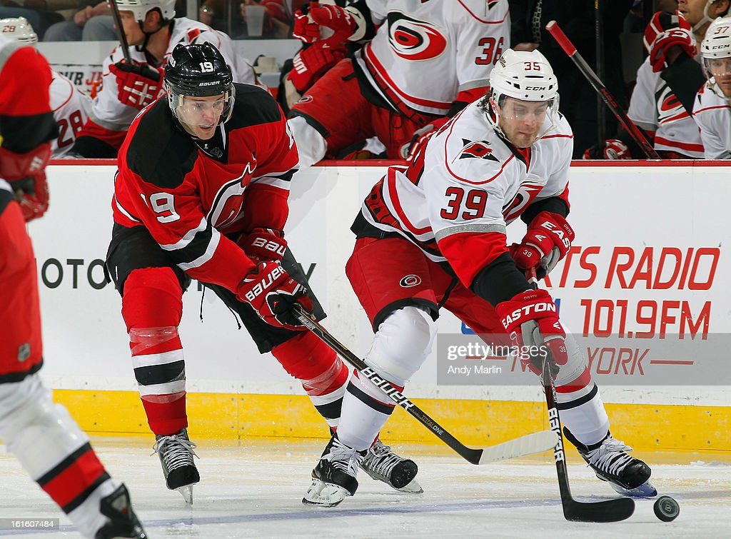 Patrick Dwyer #39 of the Carolina Hurricanes plays the puck while being defended by <a gi-track='captionPersonalityLinkClicked' href=/galleries/search?phrase=Travis+Zajac&family=editorial&specificpeople=864182 ng-click='$event.stopPropagation()'>Travis Zajac</a> #19 of the New Jersey Devils during the game at the Prudential Center on February 12, 2013 in Newark, New Jersey.