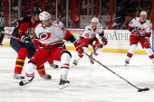 Patrick Dwyer of the Carolina Hurricanes skates for possession against Filip Kuba of the Florida Panthers at the BBT Center on March 3 2013 in...