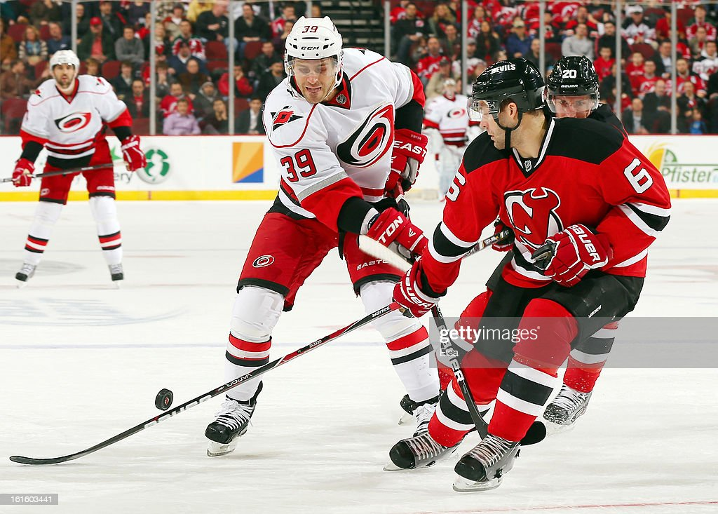 Patrick Dwyer #39 of the Carolina Hurricanes tries to take a shot as Andy Greene #6 of the New Jersey Devils defends at the Prudential Center on February 12, 2013 in Newark, New Jersey.