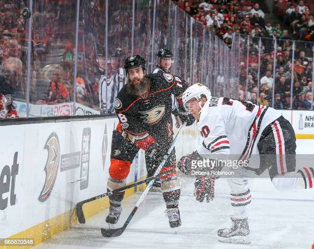Patrick Eaves of the Anaheim Ducks and Dennis Rasmussen of the Chicago Blackhawks send ice and the puck flying during the third period of the game at...