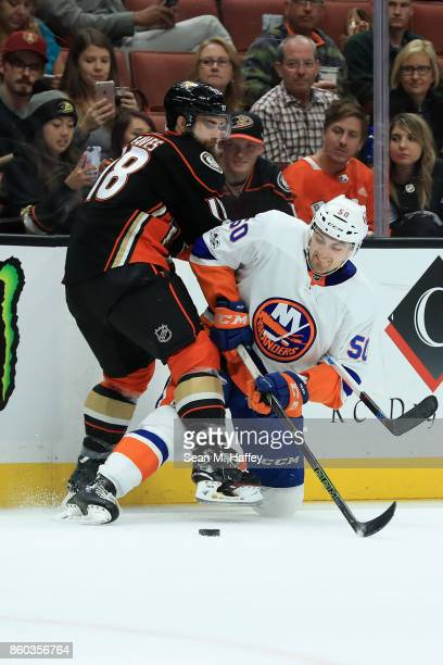 Patrick Eaves of the Anaheim Ducks battles Adam Pelech of the New York Islanders for a loose puck during the second period of a game at Honda Center...