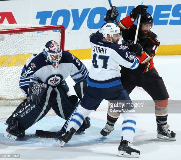 Patrick Eaves of the Anaheim Ducks battles for position against Brian Strait of the Winnipeg Jets as Michael Hutchinson holds the crease during the...