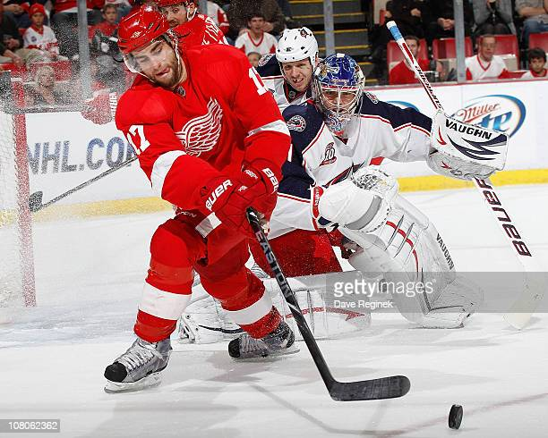 Patrick Eaves of the Detroit Red Wings reaches for the puck while Steve Mason of the Columbus Blue Jackets defends the goal during an NHL game at Joe...