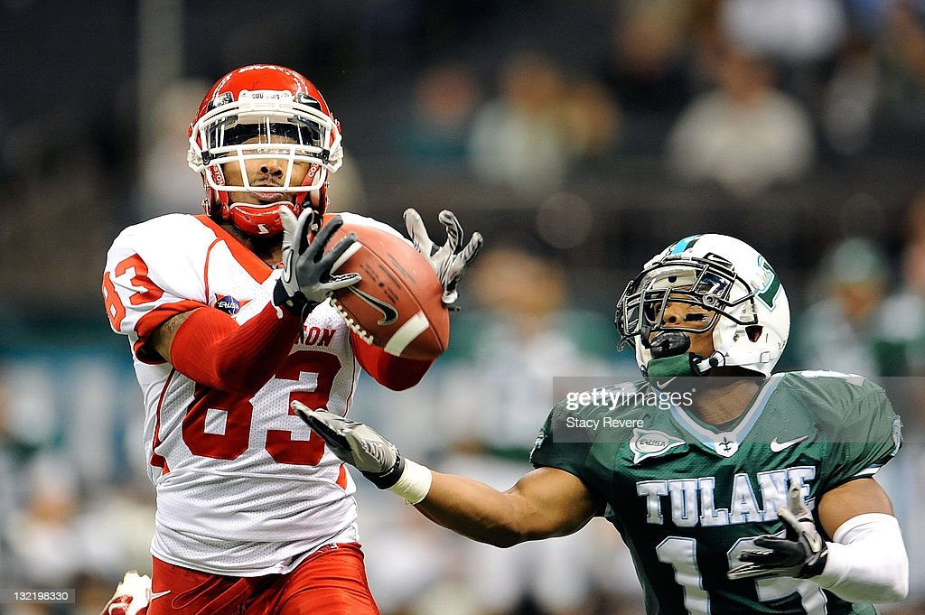 Patrick Edwards #83 of the University of Houston Cougars catches a pass over Derrick Strozier #13 of the Tulane Green Wave during a game being held at the Mercedes-Benz Superdome on November 10, 2011 in New Orleans, Louisiana.