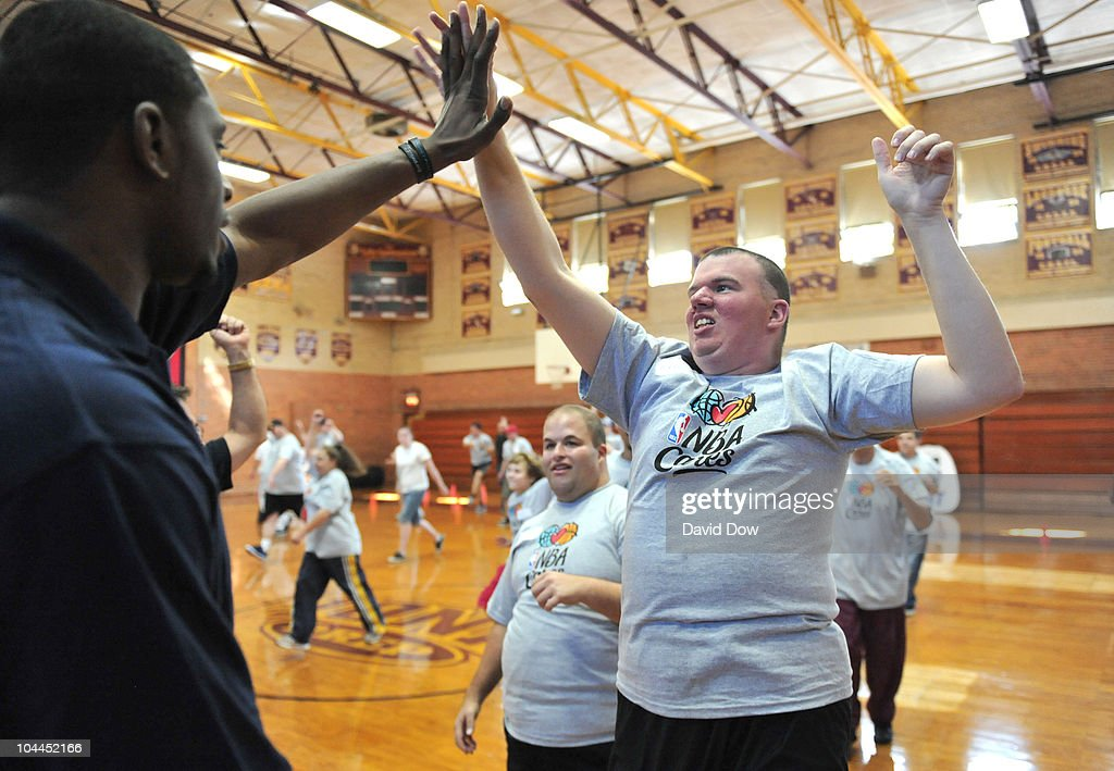 Patrick Ewing Jr. (L) of the New York Knicks high fives a participant attending the NBA Cares Special Olympic's Clinic on September 25, 2010 at Iona Preparatory High School in New Rochelle, New York.