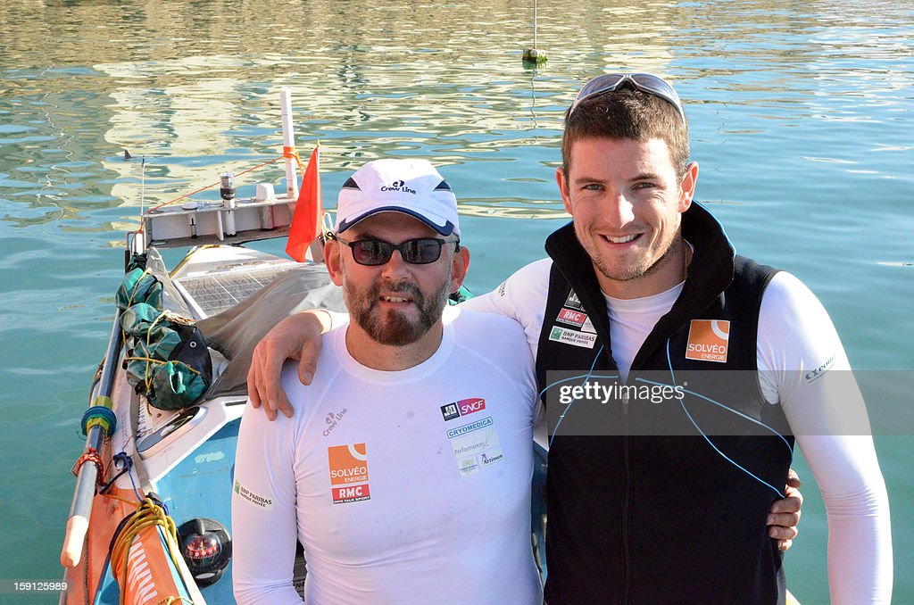 Patrick Favre (L) and Julien Bahain, French Olympic rower, poses in front of their rowing boat before their attempt at an Atlantic crossing on January 8, 2013, in Tarfaya, southern Morocco. AFP PHOTOS/STR
