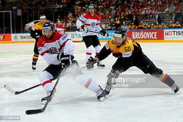 Patrick Hager of Germany and Dominique Heinrich of Austria battle for the puck during the IIHF World Championship group A match between Germany and...