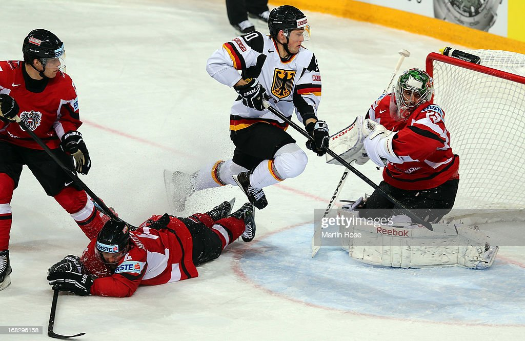 Patrick Hager (C) of Germany fails to score over Bernhard Starkbaum (R), goaltender of Austria battle for the puck during the IIHF World Championship group H match between Austria and Germany at Hartwall Areena on May 8, 2013 in Helsinki, Finland.