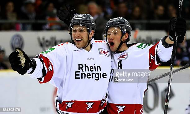 Patrick Hager of Koeln celebrate with team mate Travis Mulock during the DEL match between Grizzly Wolfsburg and Koelner Haie at BraWo Ice Arena on...