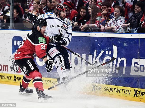 Patrick Hager of Koelner Haie challenges JeanPhillippe Cote of Iserlohn Roosters during the DEL Ice Hockey match between Koelner Haie and Iserlohn...