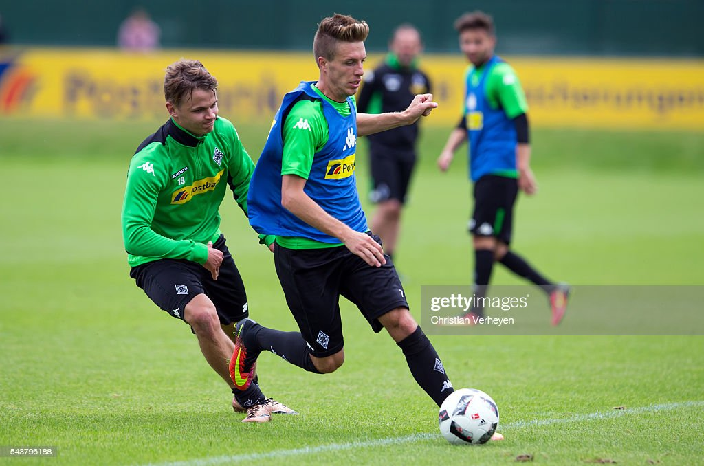 Patrick Herrmann is chased by Nils Ruetten during a training session at Borussia-Park on June 30, 2016 in Moenchengladbach, Germany.