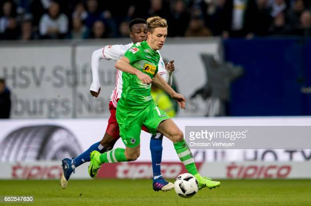 Patrick Herrmann of Borussia Moenchengladbach is chased by Gideon Jung of Hamburger SV during the Bundesliga match between Hamburger SV and Borussia...