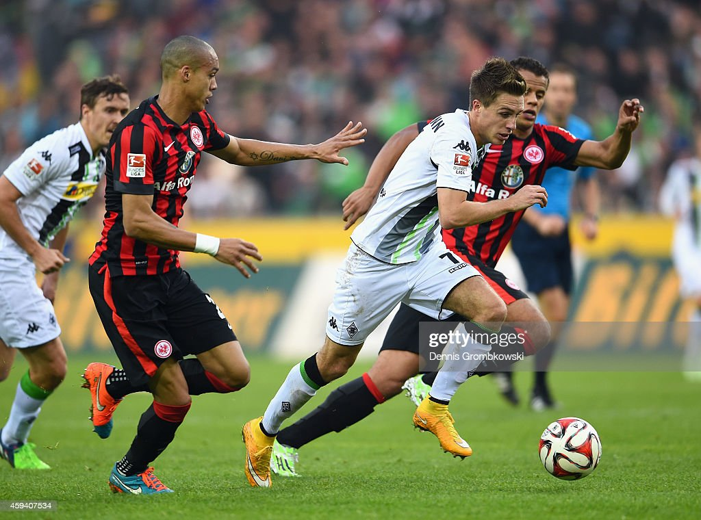 Patrick Herrmann of Borussia Moenchengladbach is chased by Timothy Chandler and Bamba Anderson of Eintracht Frankfurt during the Bundesliga match between Borussia Moenchengladbach and Eintracht Frankfurt at Borussia Park Stadium on November 22, 2014 in Moenchengladbach, Germany.