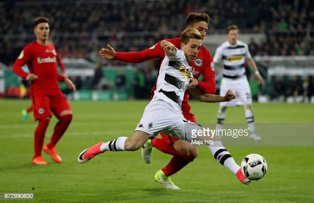 Patrick Herrmann of Moenchengladbach and Bastian Oczipka of Frankfurt battle for the ball during the DFB Cup semi final match between Borussia...
