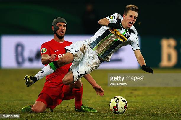 Patrick Herrmann of Moenchengladbach is challenged by Klaus Gjasula of Offenbach during the DFB Cup Round of 16 match between Kickers Offenbach and...