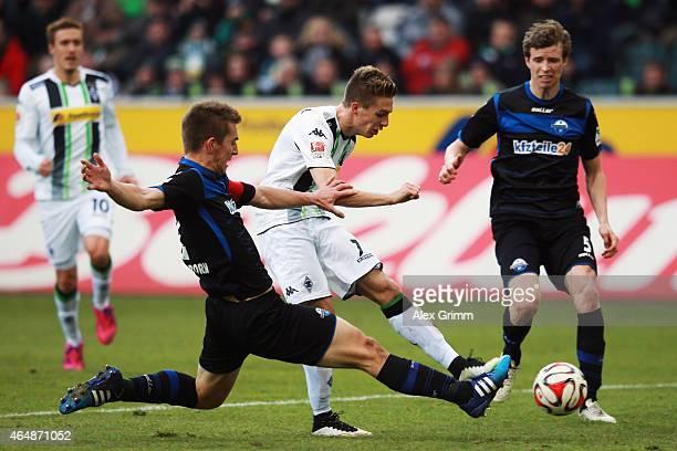 Patrick Herrmann of Moenchengladbach is challenged by Uwe Huenemeier of Paderborn during the Bundesliga match between Borussia Moenchengladbach and...