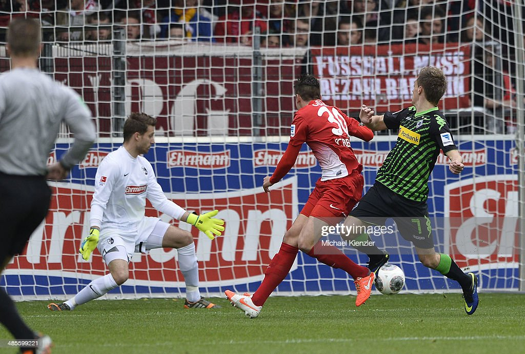 Patrick Herrmann (R) of Moenchengladbach shoots against Oliver Baumann (L) and Christian Guenter (C) of Freiburg during the Bundesliga match between SC Freiburg and Borussia Moenchengladbach at Mage Solar Stadium on April 19, 2014 in Freiburg, Germany.