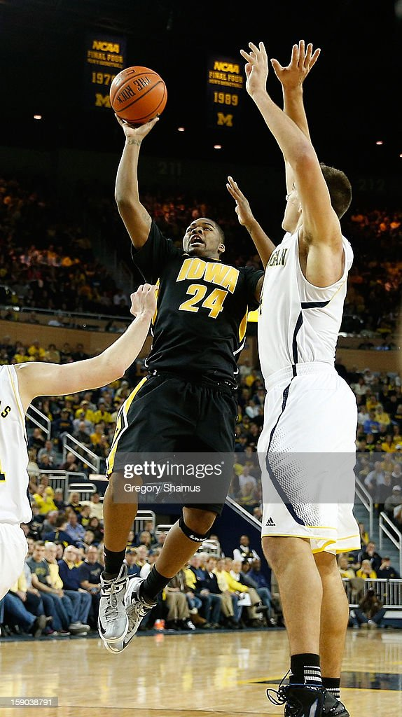 Patrick Ingram #24 of the Iowa Hawkeyes gets off a second half shot off next to Mitch McGary #4 of the Michigan Wolverines at Crisler Center on January 6, 2013 in Ann Arbor, Michigan. Michigan won the game 95-67.