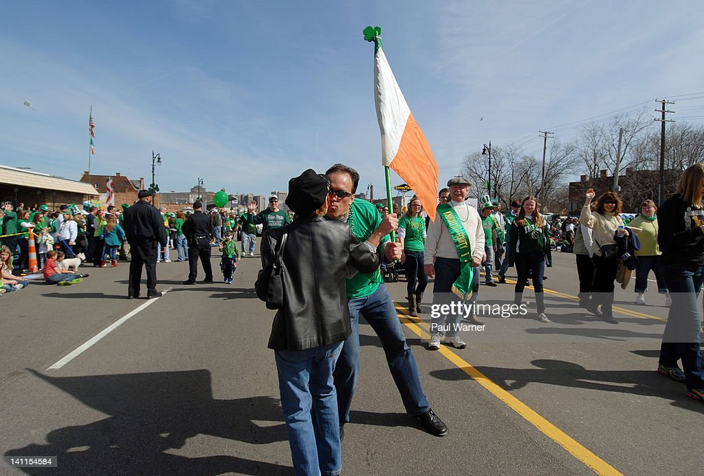 Patrick Irwin receives a kiss from a friend while holding the flag of Ireland as he attends the St. Patrick's Day Parade on the streets of Detroit on March 11, 2012 in Detroit, Michigan.