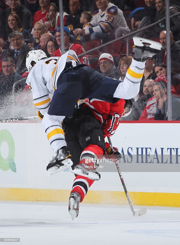 Patrick Kaleta of the Buffalo Sabres goes flying through the air after being checked by Anton Volchenkov of the New Jersey Devils during the game at...