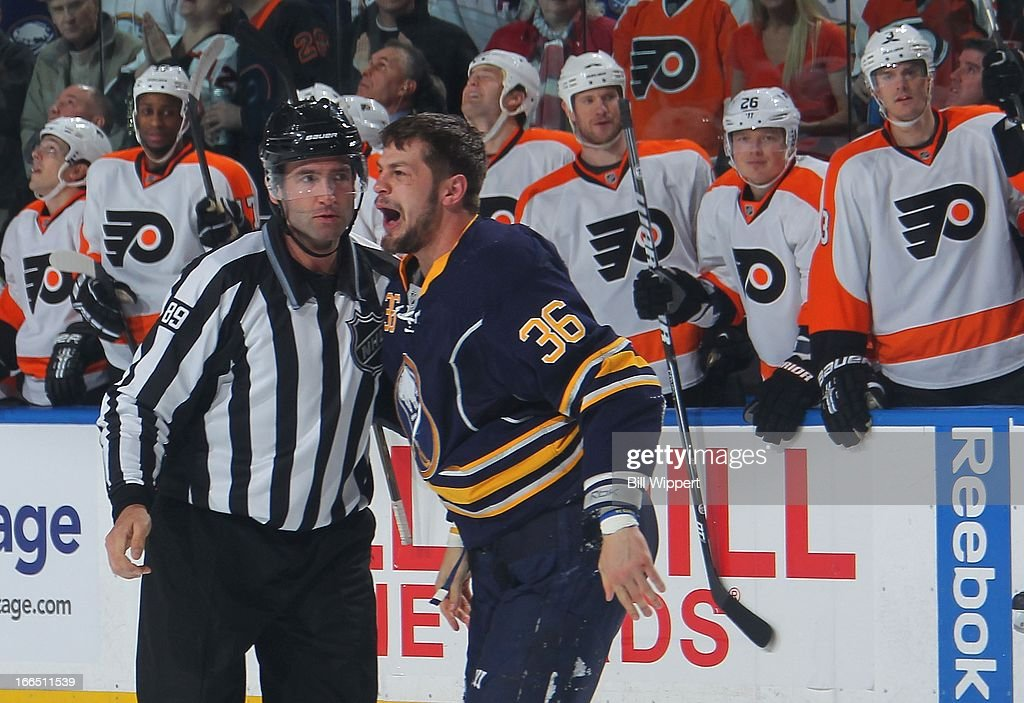Patrick Kaleta of the Buffalo Sabres is escorted to the penalty box by linesman Steve Miller after a fight in the first period against the...