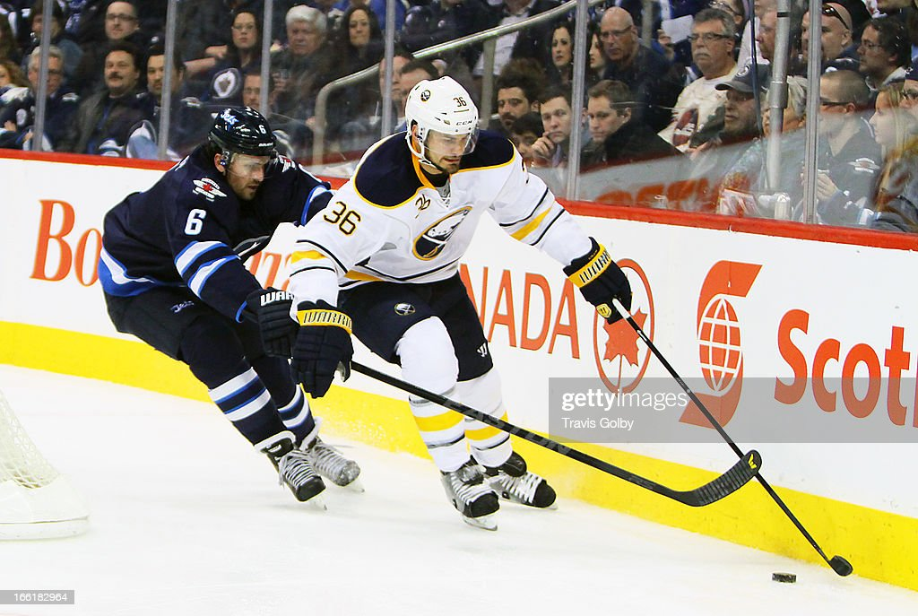 Patrick Kaleta #36 of the Buffalo Sabres plays the puck along the board as Ron Hainsey #6 of the Winnipeg Jets defends during second-period action at the MTS Centre on April 9, 2013 in Winnipeg, Manitoba, Canada.