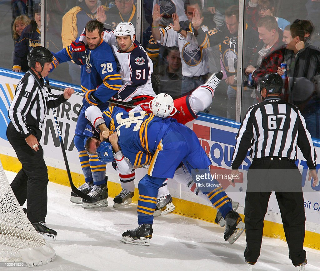 Patrick Kaleta of the Buffalo Sabres takes down Cody Bass of the Columbus Blue Jackets during a fight as Paul Gaustad of the Sabres and Fedor Tyutin...