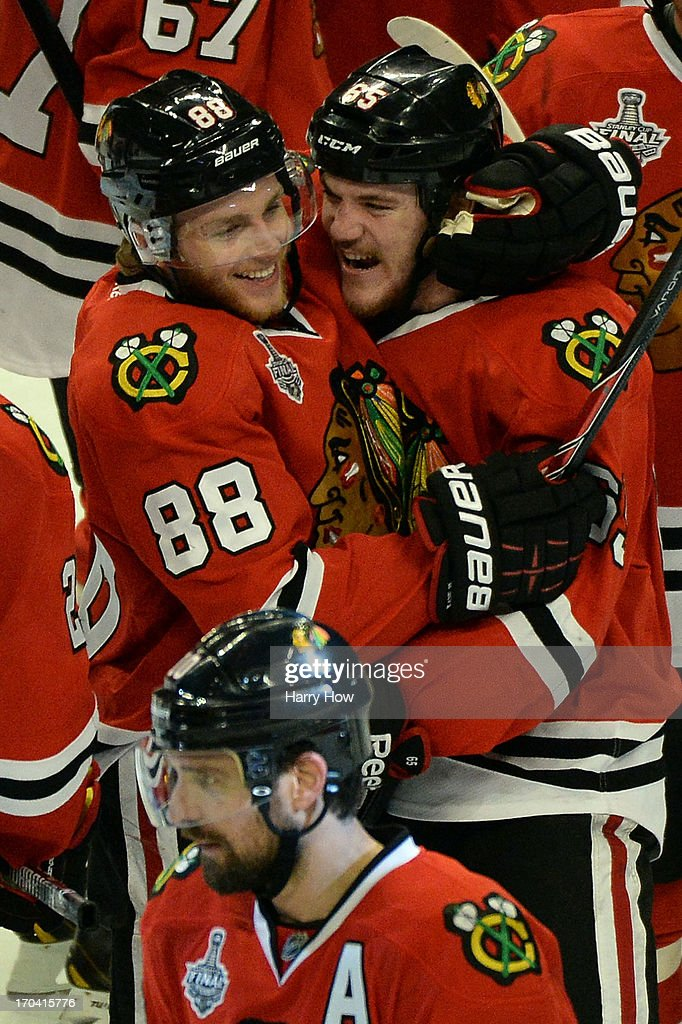 Patrick Kane #88 and Andrew Shaw #65 of the Chicago Blackhawks celebrate after Shaw scored the game-winning goal in the third overtime to give them a 4-3 win against the Boston Bruins in Game One of the 2013 NHL Stanley Cup Final at United Center on June 12, 2013 in Chicago, Illinois.